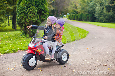 Adorable little girls riding on motobike in the
