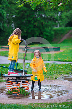 Adorable little girls under the rain having fun outdoor Stock Photo