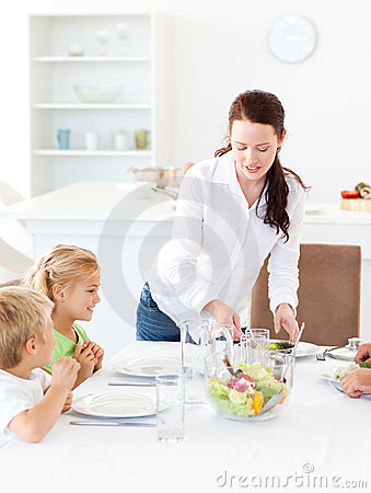 Adorable mother serving salad to her children