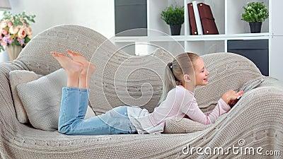 Adorable petite fille domestique pieds nus qui rit en s'amusant à regarder l'écran de la tablette PC clips vidéos