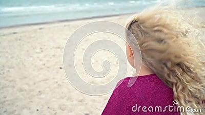 Adorable petite fille en chandail violet traversant la côte maritime clips vidéos