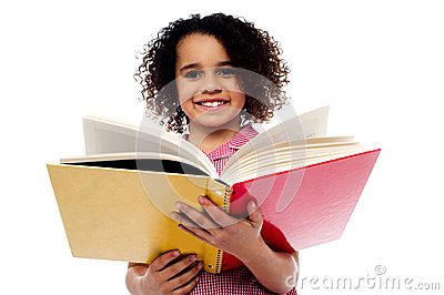 Adorable school girl reading a book with a smile