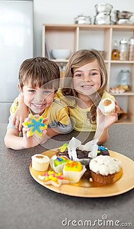 Adorable siblings showing their cookies