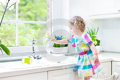 Adorable toddler girl in colorful dress washing dishes