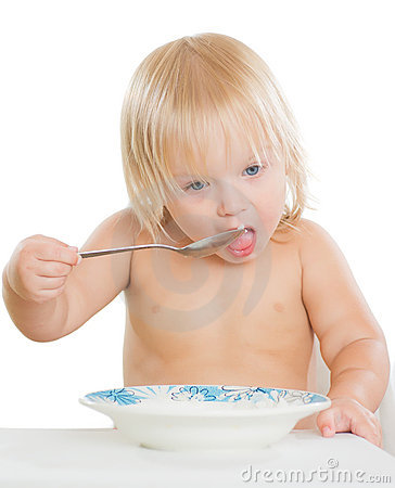 Adorable toddler girl eat porridge