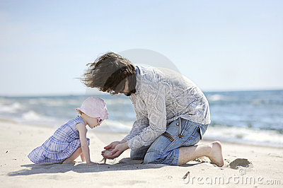 Adorable toddler girl and her father on a beach