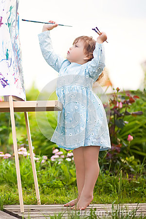 Adorable toddler girl painting on the easel in the garden Stock Photo