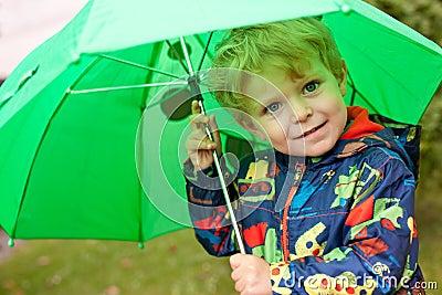 Adorable toddler under green rain umbrella autumn