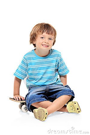 Adorable young boy sitting on a skateboard