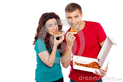 Adorable young couple relishing yummy pizza