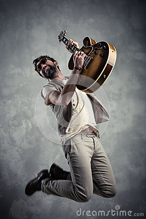 Free Adult Caucasian Guitarist Portrait Playing Electric Guitar And Jumping On Grunge Background. Music Singer Modern Concept Royalty Free Stock Images - 92525919