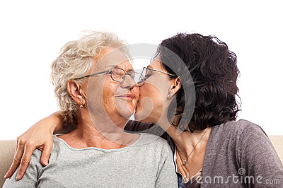 Adult daughter giving old mom a kiss