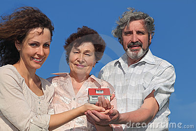 Adult daughter and parents holding house model Stock Photo