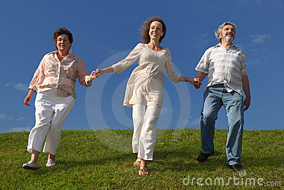 Adult daughter and parents walking on lawn Stock Photo