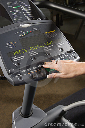 Adult female setting up elliptical machine.