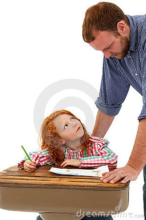 Adult helping School Child at Desk