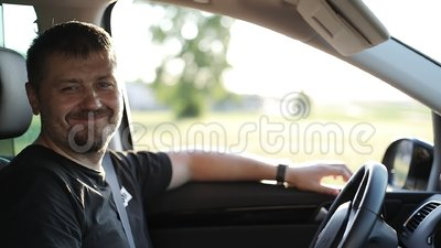 An adult man with a beard is sitting in the car and smiling  The driver  sits in the front seat of the vehicle