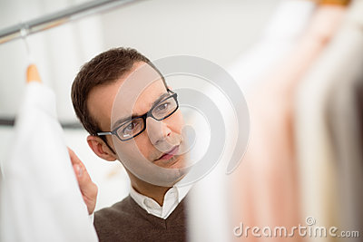 Adult man choosing shirt in clothes shop