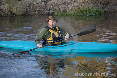 Adult paddler in blue kayak