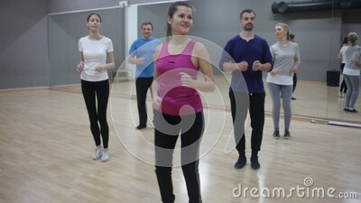 Smiling females and males doing Zumba dance workout during group classes in fitness center. Of adult people training in gym, doing aerobics exercises stock video footage