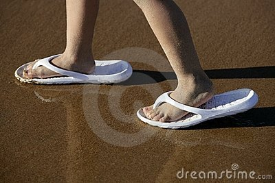 Adult shoes for children feet on beach sand