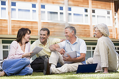 Adult students sitting on a campus lawn