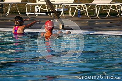 Adult teaching child to swim