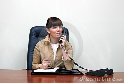Adult white woman behind a desk in an office talking on