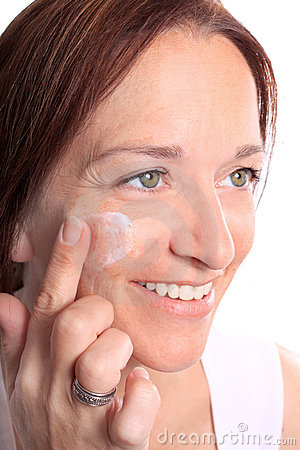 Adult woman applies cream on face