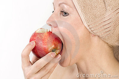 Adult woman is biting an apple.