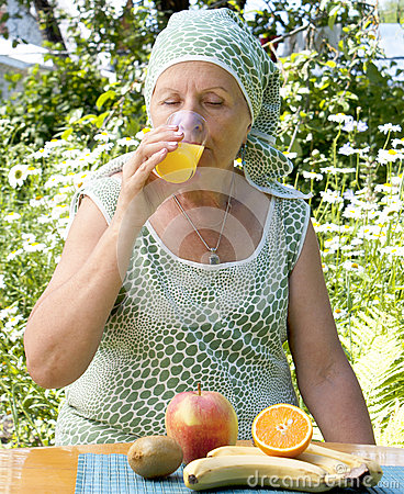 The  adult woman drinks fresh orange juice