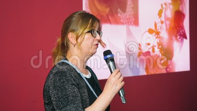 Adult woman holding microphone and speaking on performance stage at event. Cheerful woman with microphone speaking celebratory speech at festive event stock video footage
