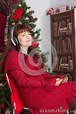 Adult woman listening music against Christmas tree