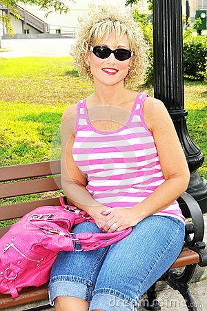 Adult woman siting on a park bench with pink purse