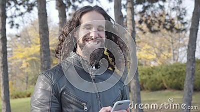 Adulte Rocker aus dem Nahen Osten mit langen, lockig schwarzen Haaren, die Smartphone mit Musik in Kopfhörern halten Positiv stock footage