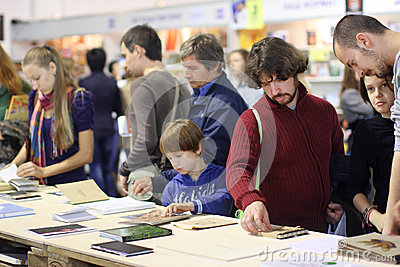 Adults and a child read the books at the book fair Editorial Stock Photo
