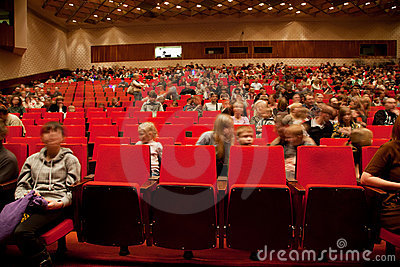 Adults and children sit on red chairs