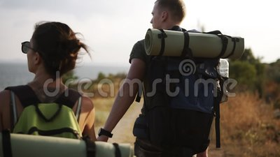 Adventure, travel, tourism, hike and people concept. Rare footage of a couple hiling the hills together with backpacks. Morning sun stock video