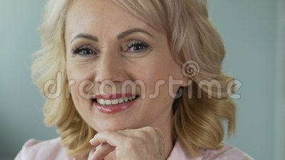 Advertising of anti-age cosmetics. Attractive mature woman smiling into camera. Stock footage stock video footage