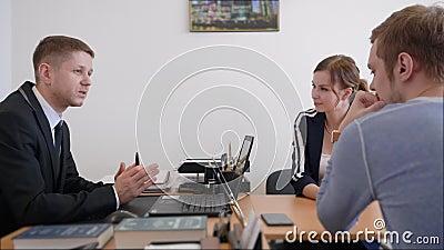 Advogado amigável ou conselheiro financeiro no terno que consultam pares novos, o corretor de sorriso do investimento ou a fatura vídeos de arquivo