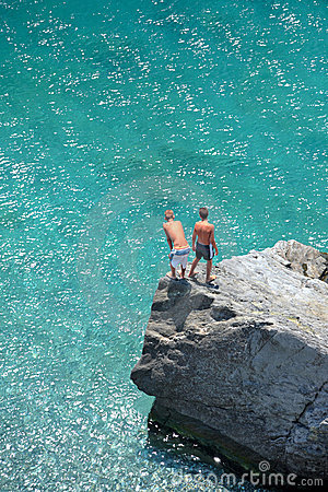 Aerial photo of two young boys on rock looking into sea