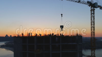 Aerial shot of construction site with cranes and workers at sunset stock footage