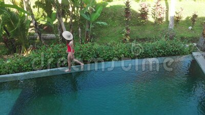 aerial top down view infinity pool luxurious exotic island woman walking edge pool enjoy jungle view wearing red 178945747
