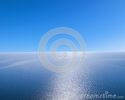 Aerial view of a blue sea water background and sun reflections. Aerial flying drone view. Waves water surface texture on sunny tro Stock Photo