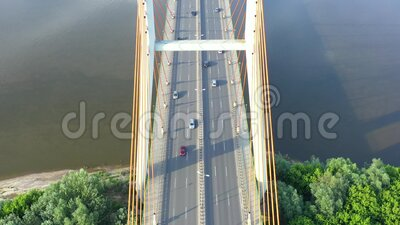 Aerial view of car traffic on modern bridge over river in city in summer day stock footage