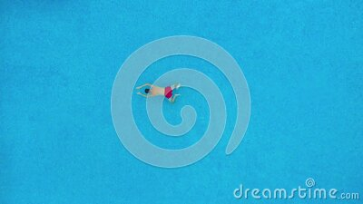 Aerial view of man in red shorts swims under the water in the pool. stock video footage