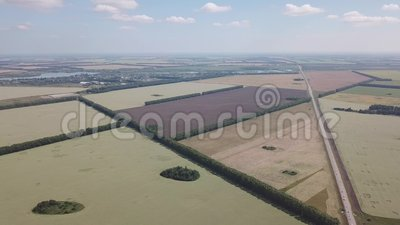 Aerial view rotating 360 degrees above the road in the middle of a large number of colorful fields planted with plants for agricul. Ture on a sunny autumn day stock video footage