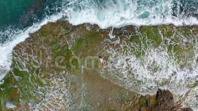 AERIAL VIEW. Sea waves splashing with foam and spray to stony coast. Beautiful woman lies on rocky beach. AERIAL VIEW. Sea waves splashing with foam and spray stock video