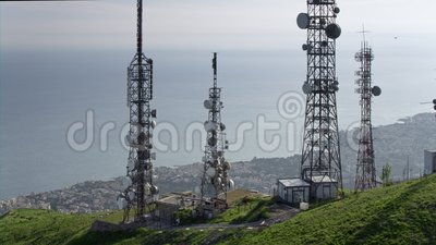 Aerial view of telecommunications towers antennas and cityscape in the background stock footage