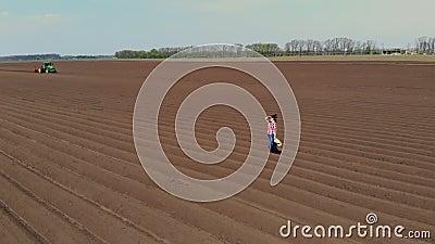 Aero Agronomista camina en el campo con filas especiales de tierra Ella prueba, usando tableta, la calidad de la papeleta automat metrajes